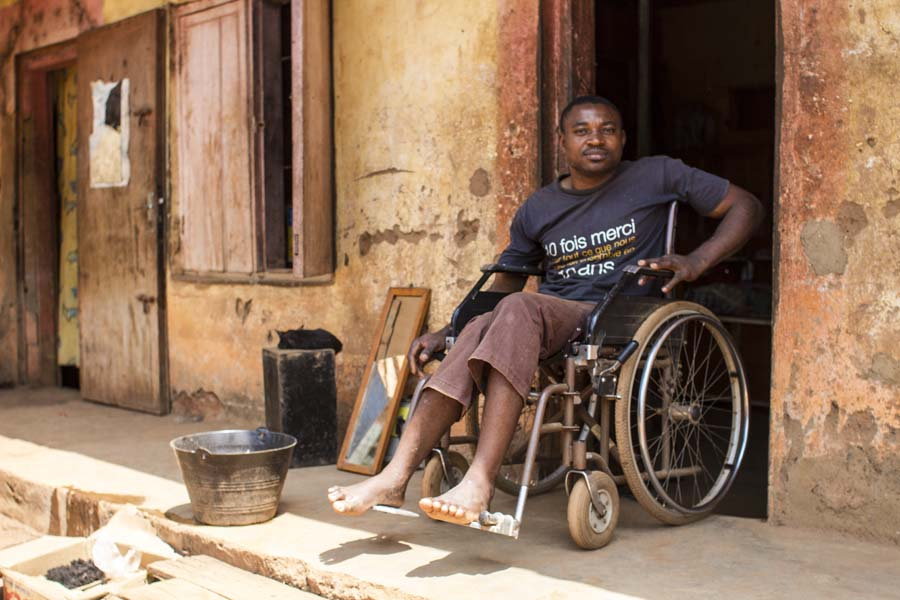 This 35 year old man became disabled when he was 21 years old from an injury.  His spine became dislocated when he lifted heavy objects.  He believes that he would not have been disabled as he is today if he had better quality of health care.  The doctors did not identify his injury quickly enough to repair his spine to the point that he could maybe walk again.  He spends most of his days in his shop which is clearly also his home as his bed was in the shop too.  He sends neighbors to get water and sometimes pays them.